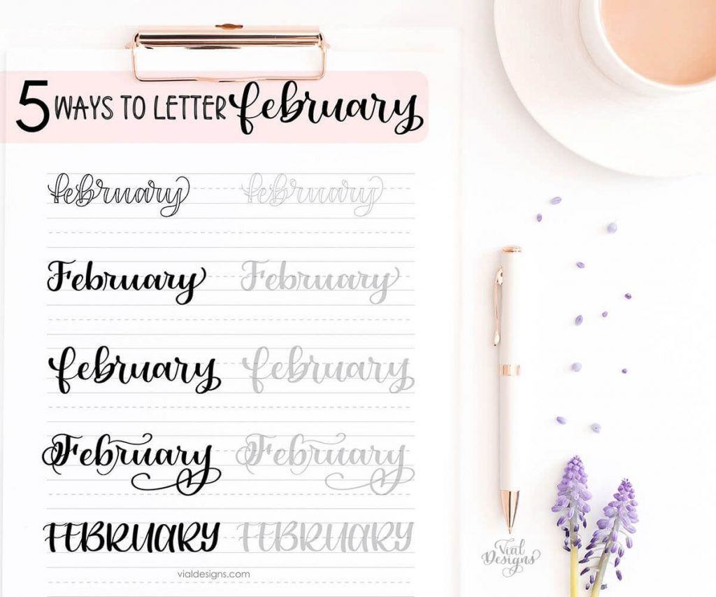 5 Ways to Letter February Lettering Practice Sheet Displayed on a clipboard on a flat lay with a rose gold pen, a late, and lavender