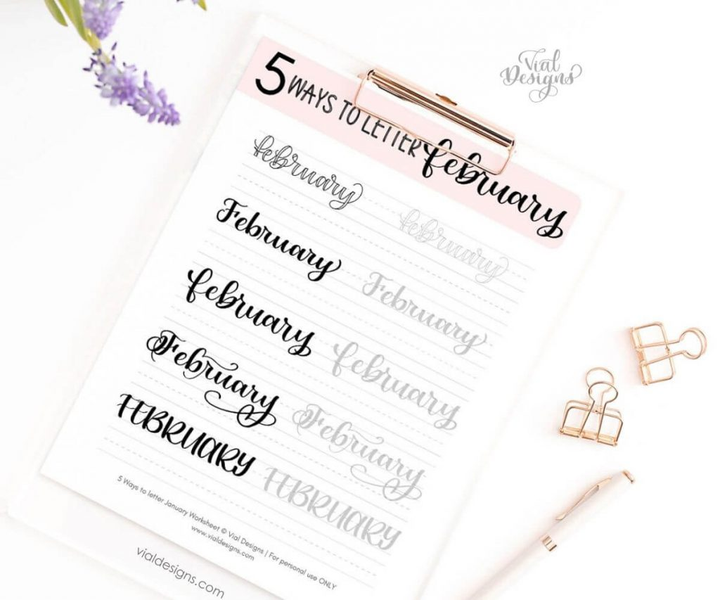 5 Ways to letter February Lettering Practice Sheet displayed on a keyboard flatlay with a pen and pretty paper clips around it