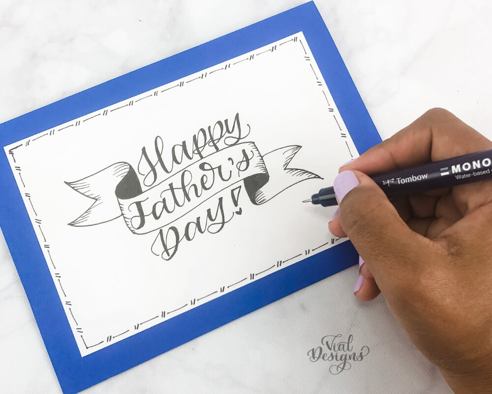 Happy Father's Day lettered on a ribbon on white cardstock