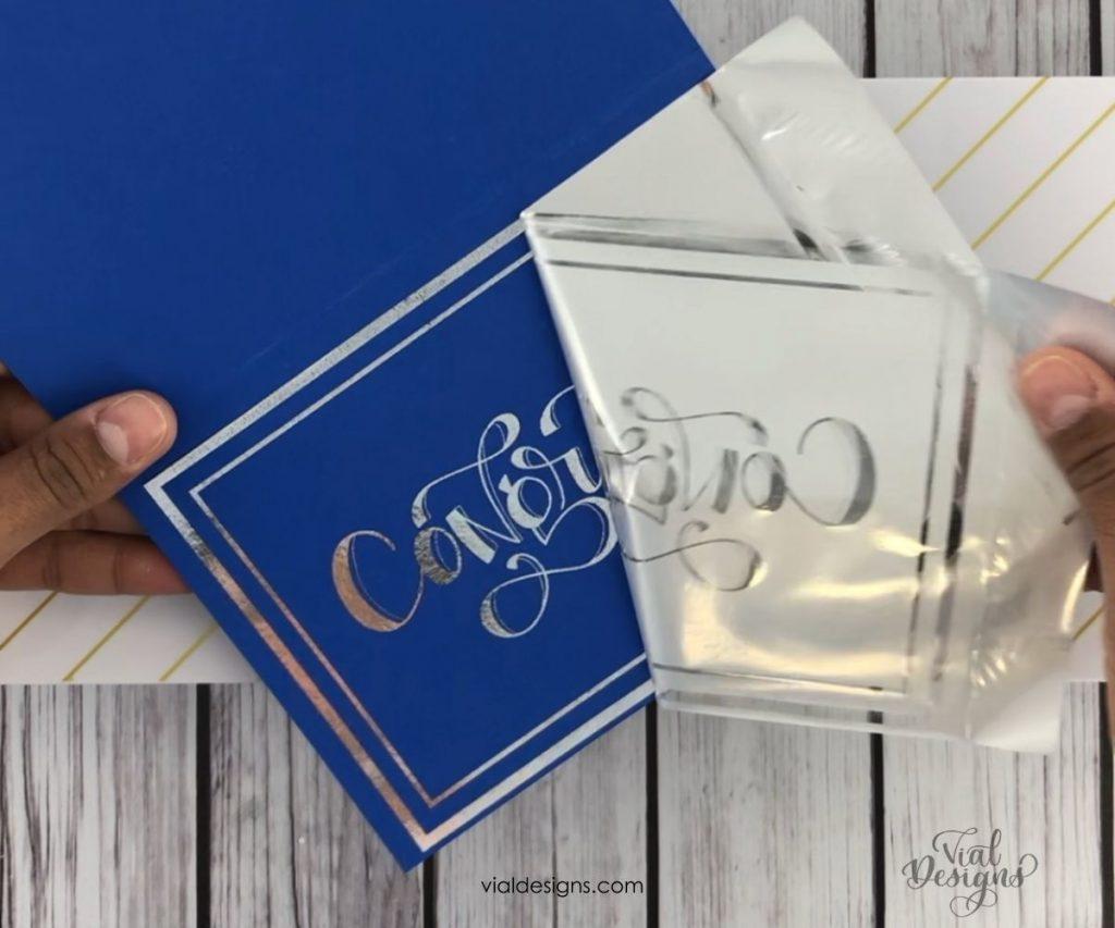 peeling the silver foil off the royal blue congrats card